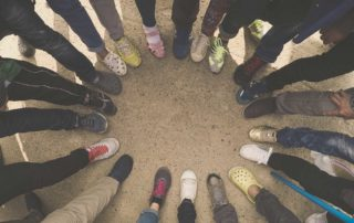 view of people's feet while standing in a circle