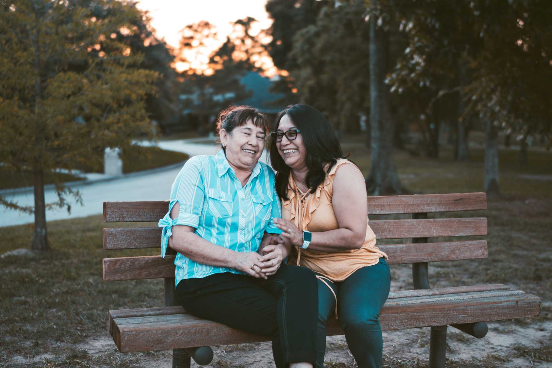 two older women laughing together on a park bench