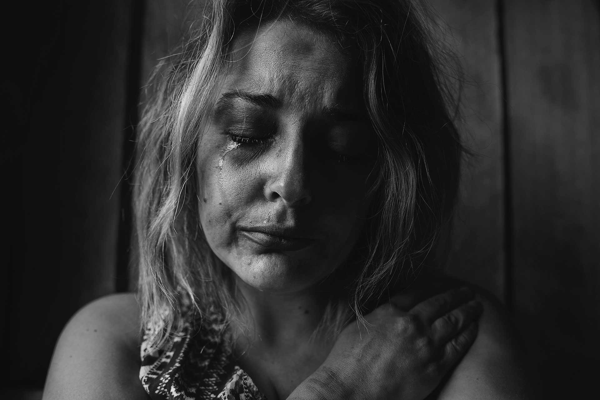 grayscale photo of woman crying