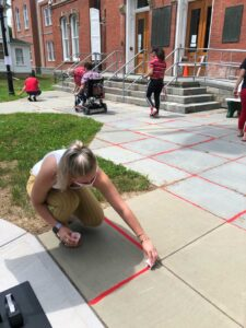 vip employees pouring red sand in cracks for human trafficking awareness